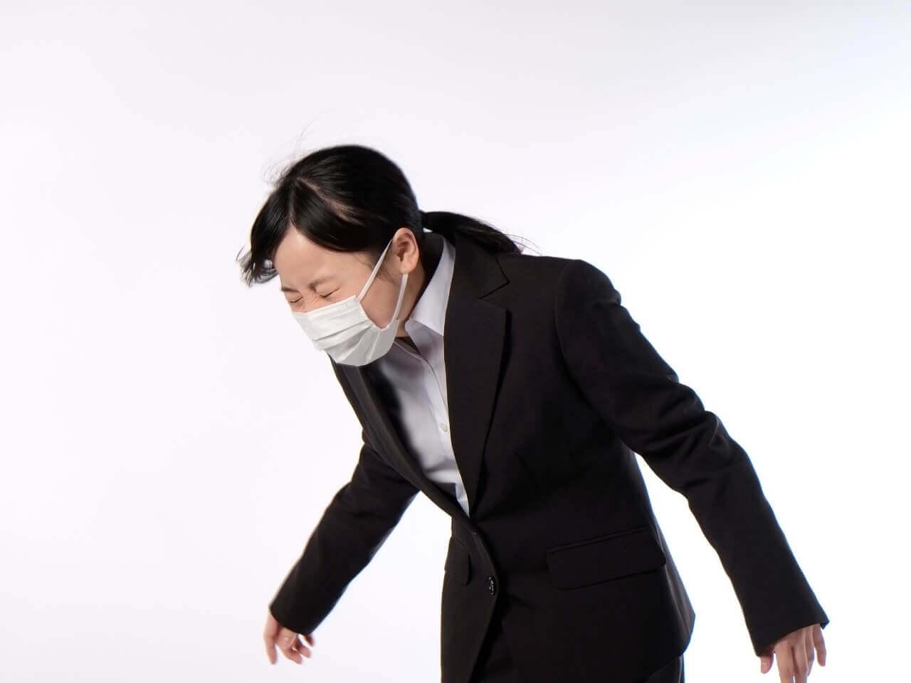 マスクをつけてくしゃみをする女性