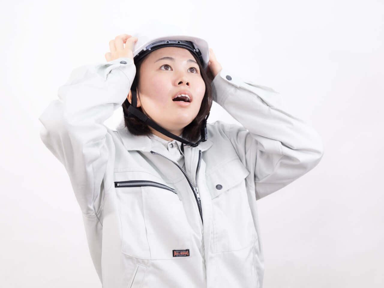 身を守るヘルメットをかぶった作業服の女性