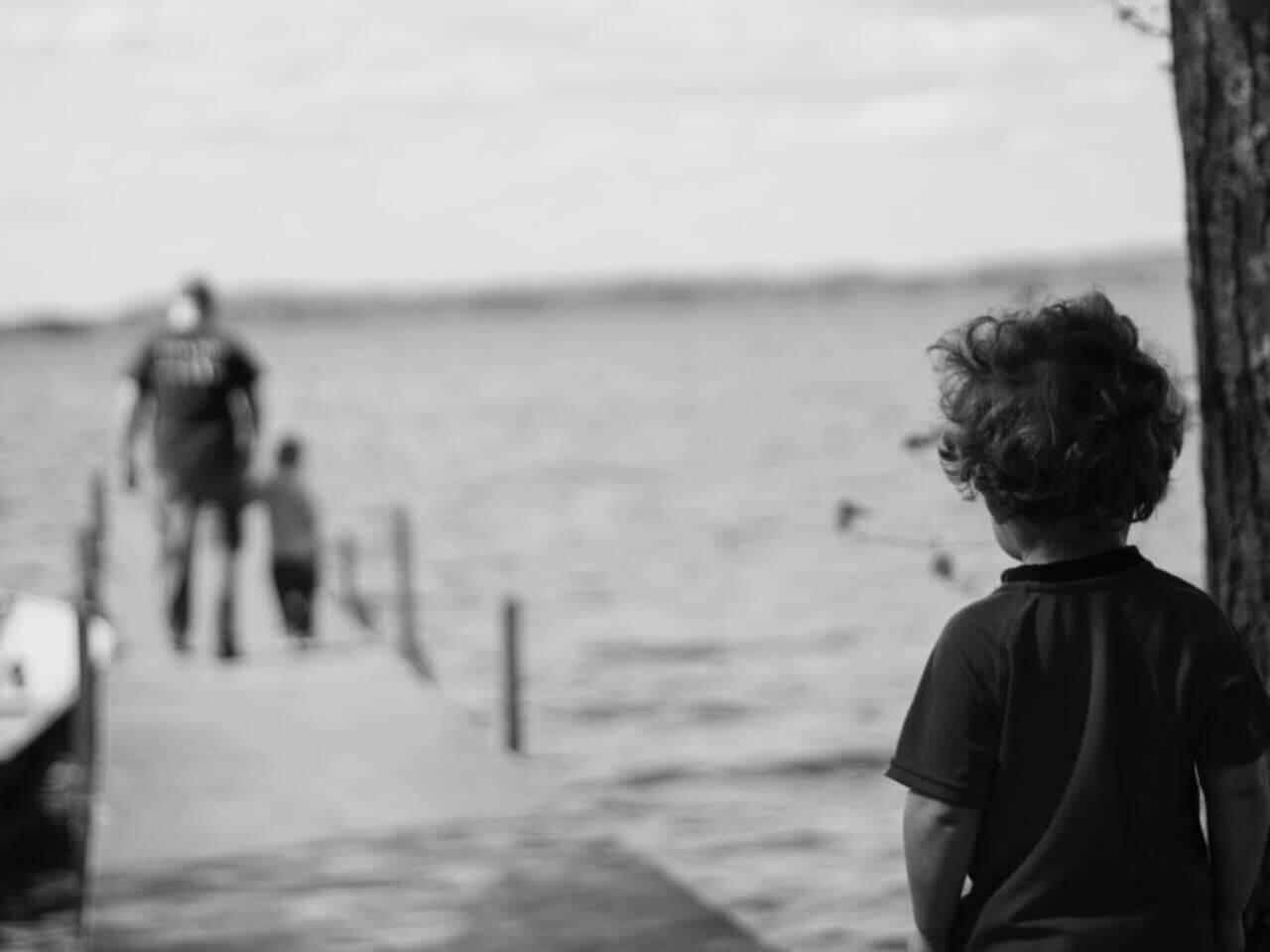 ひとりぼっちで親子を見つめる少年