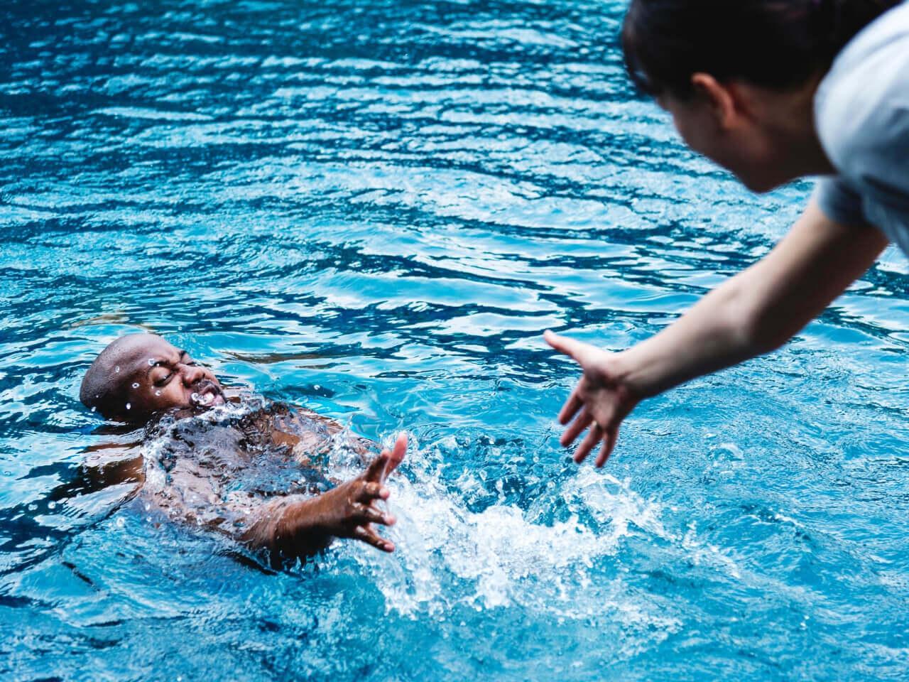 溺れる男性を救助する女性