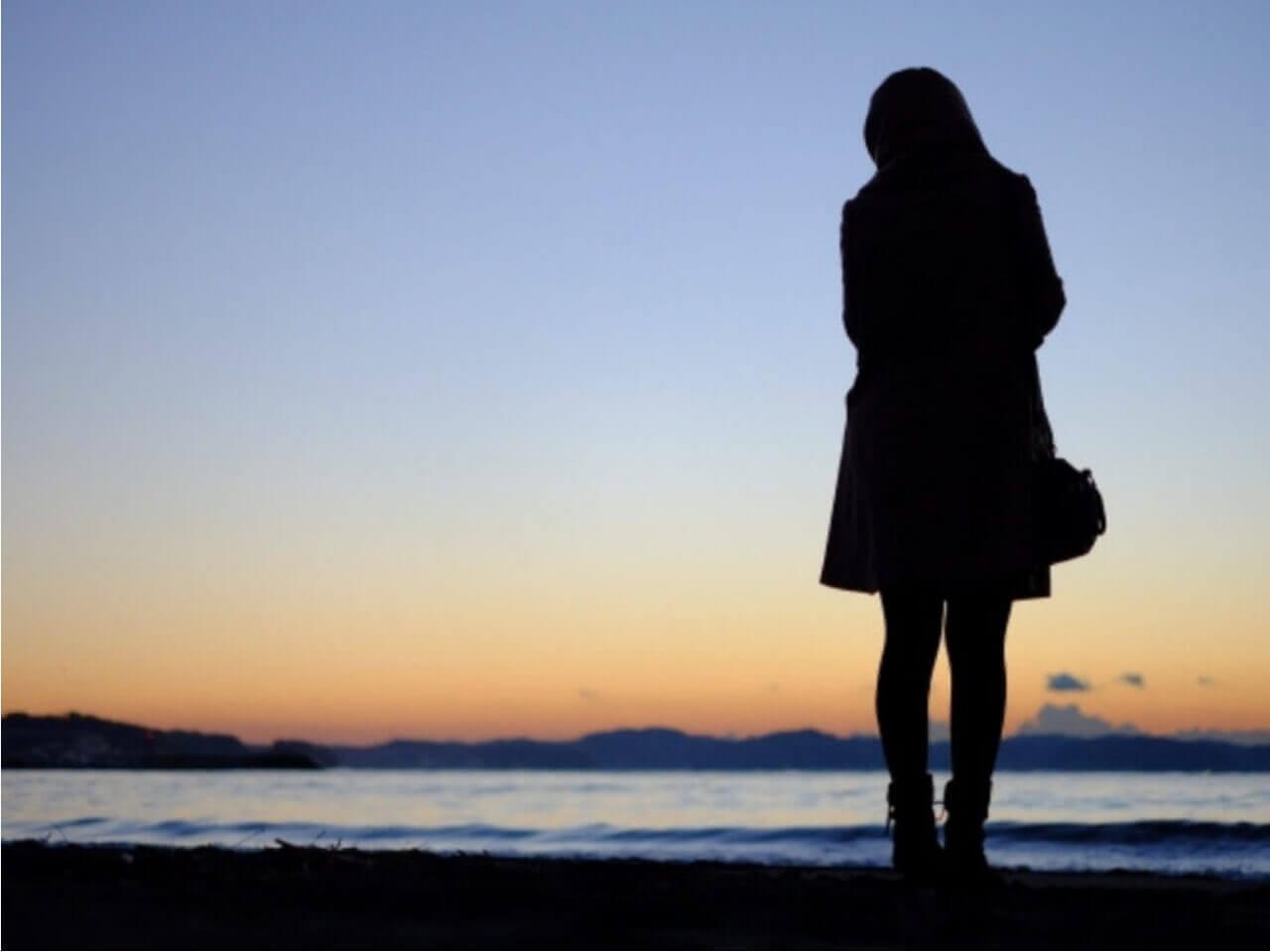 夕暮れの海でひとりぼっちの女性