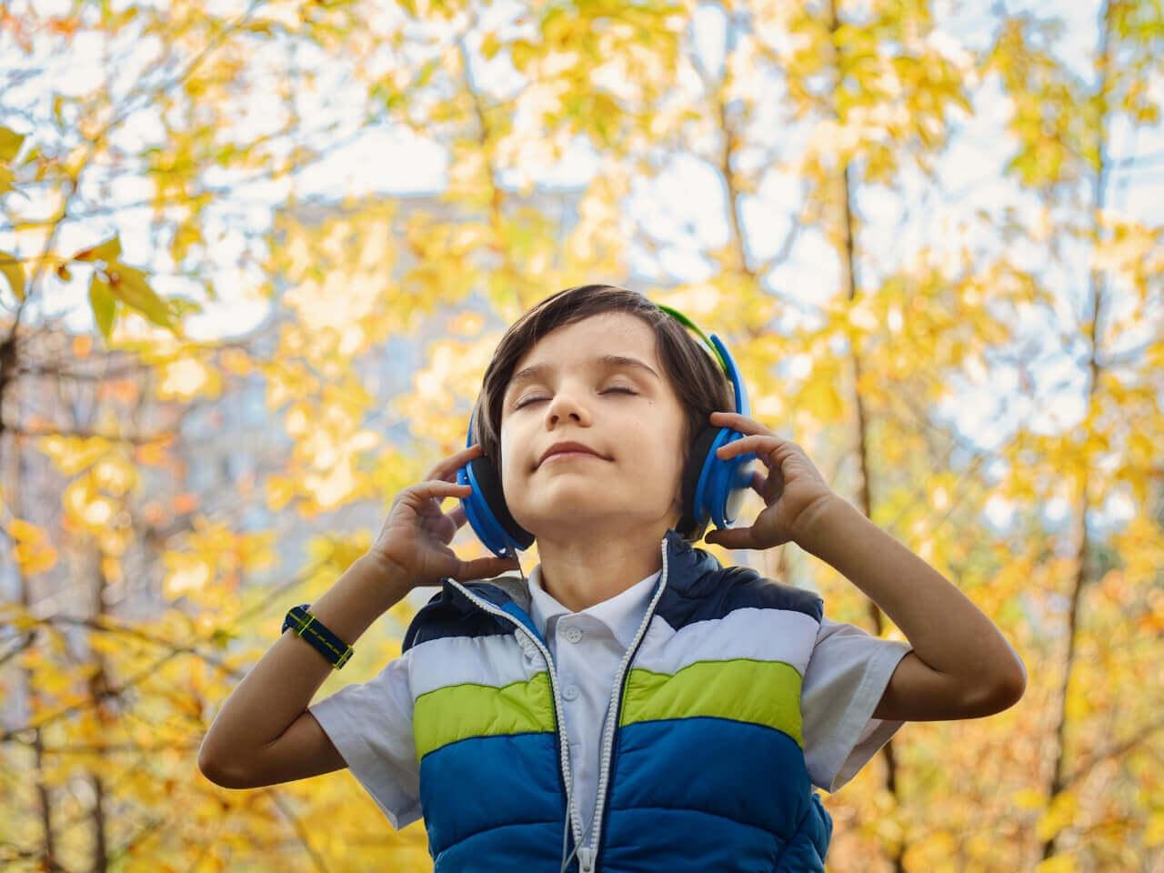 静かな森でヘッドホンで音楽を聞く少年