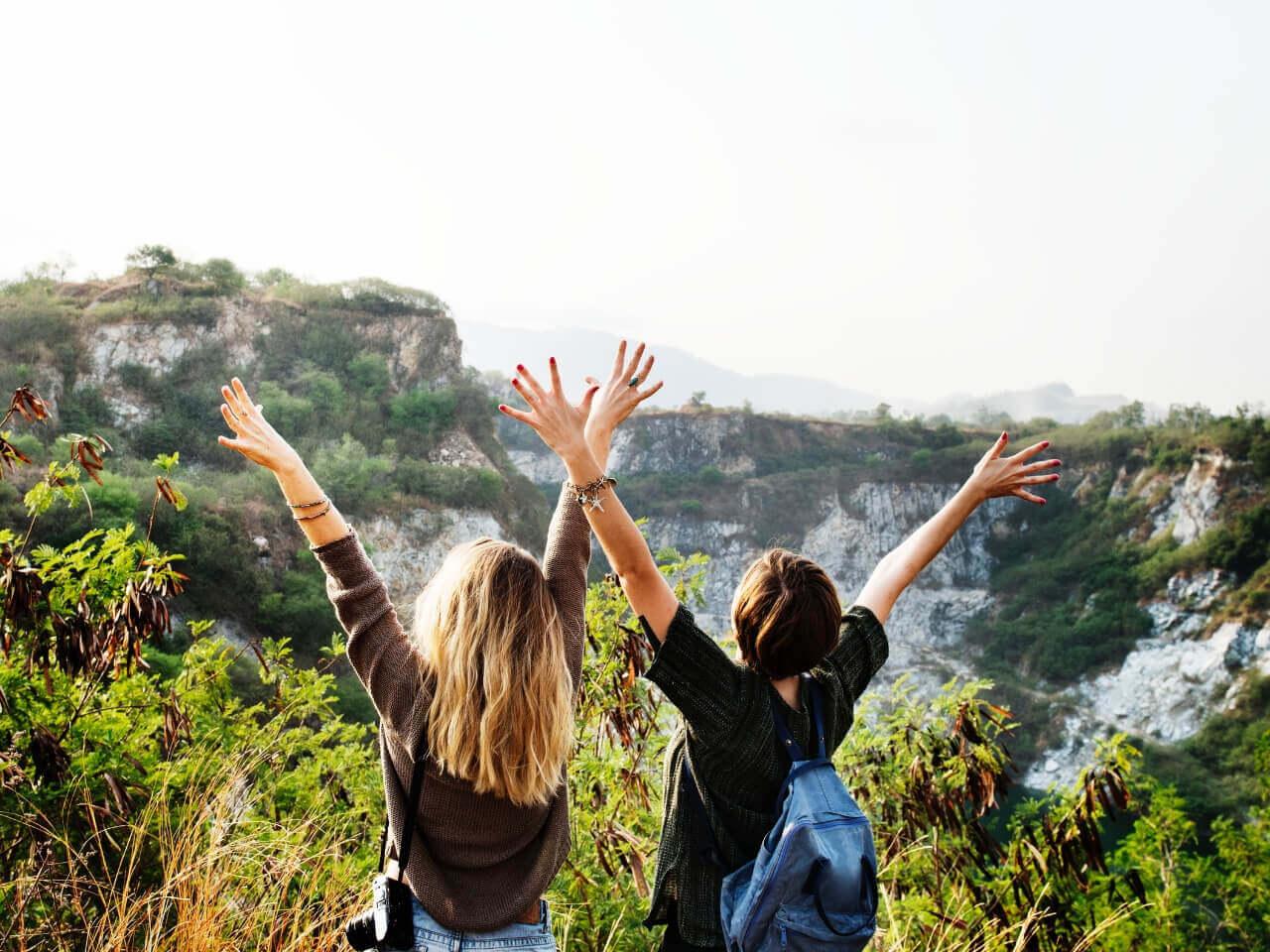 山登りでバンザイして喜ぶ女性二人
