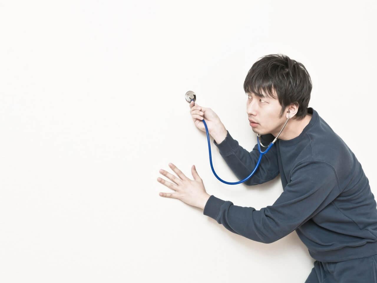 聴診器で隣の部屋の音を聞く男性