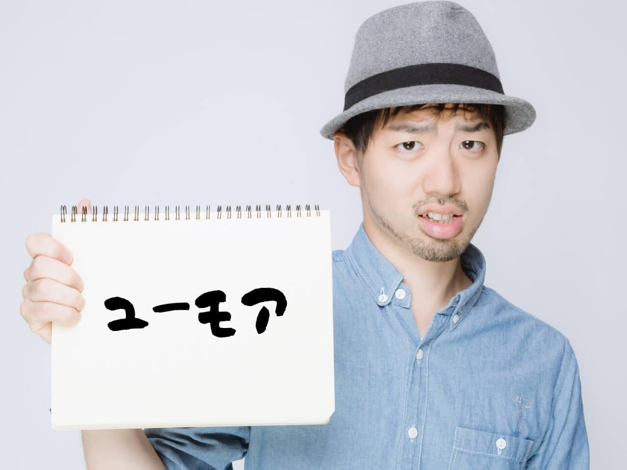 「ユーモア」と書かれたスケッチブックを持つ男性