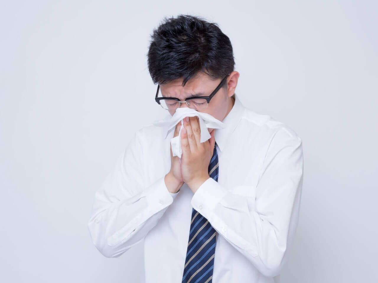 紙で鼻をかむ男性