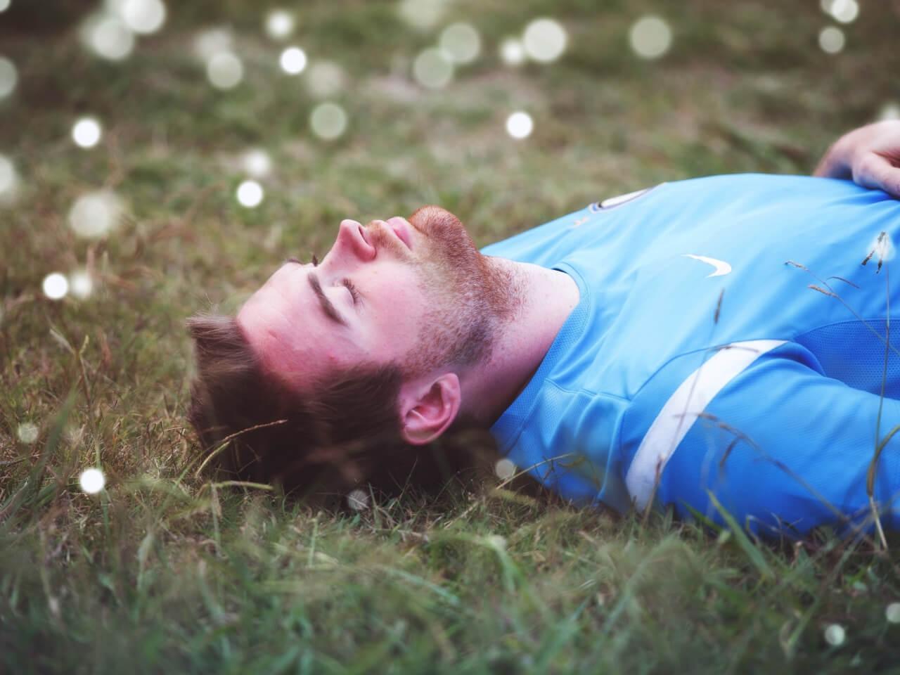 芝生の上で眠る男性
