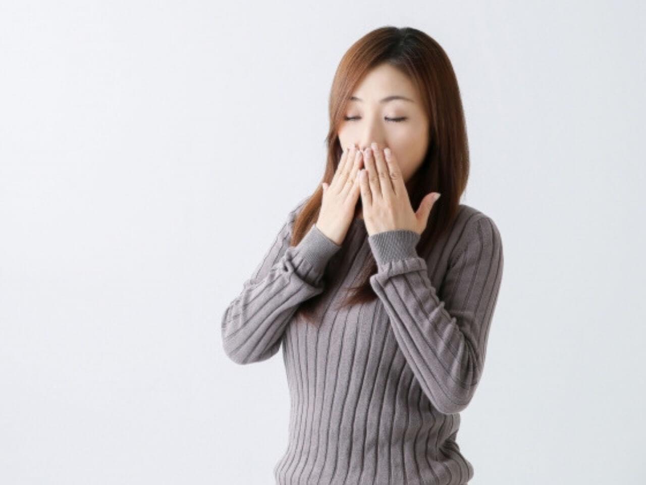 両手で隠しながらあくびをする女性