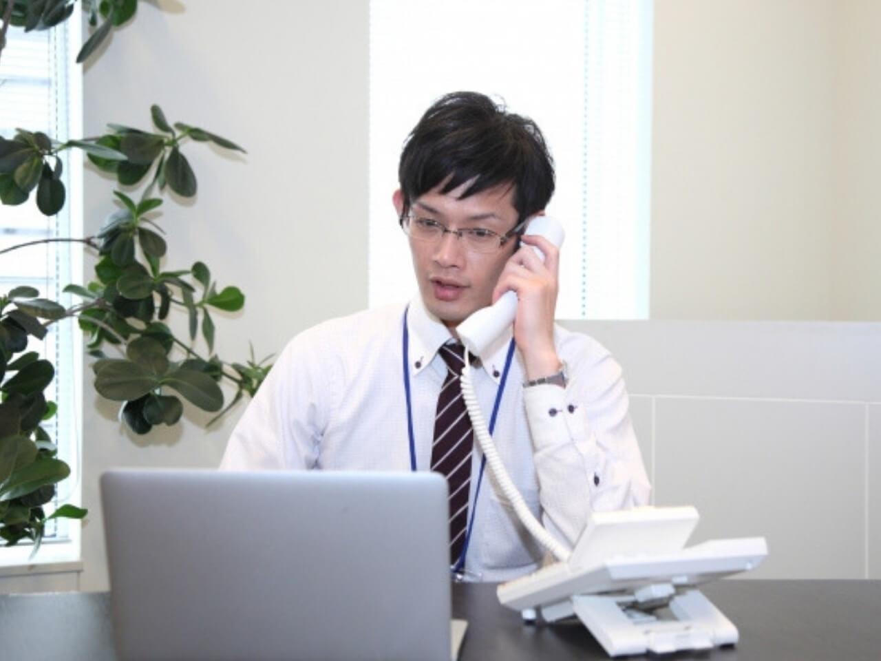 不安そうに電話対応する男性
