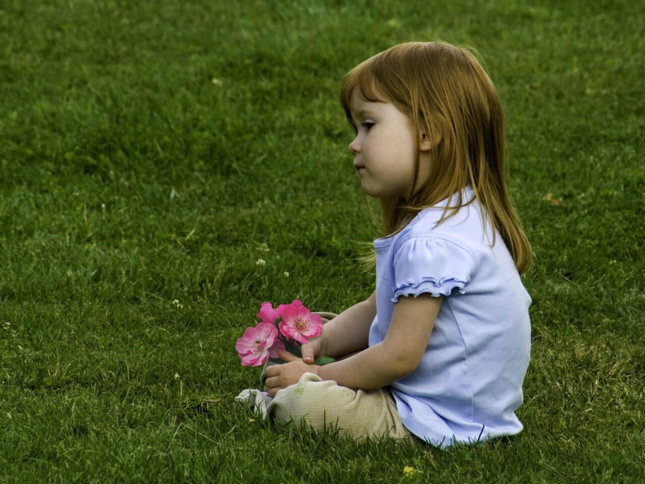 芝生に座って自然な様子の女の子