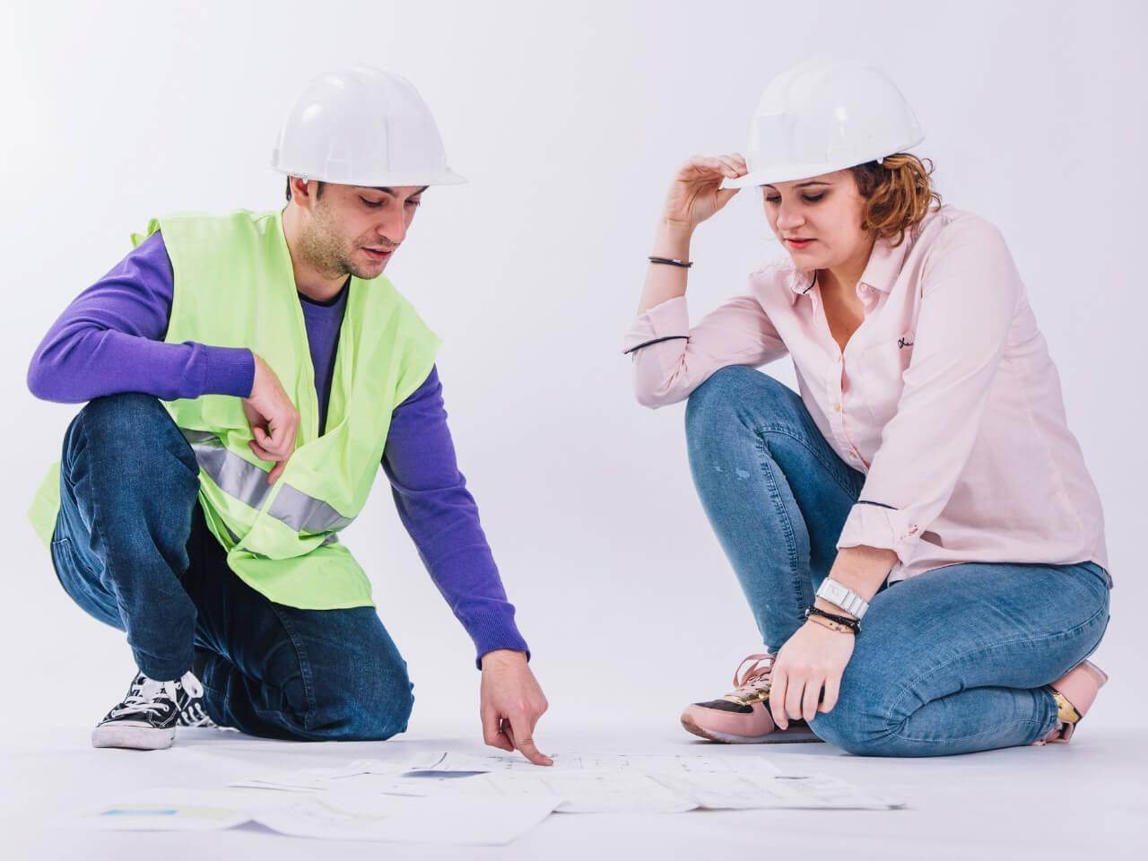 建設計画を話し合うヘルメットをかぶった男女