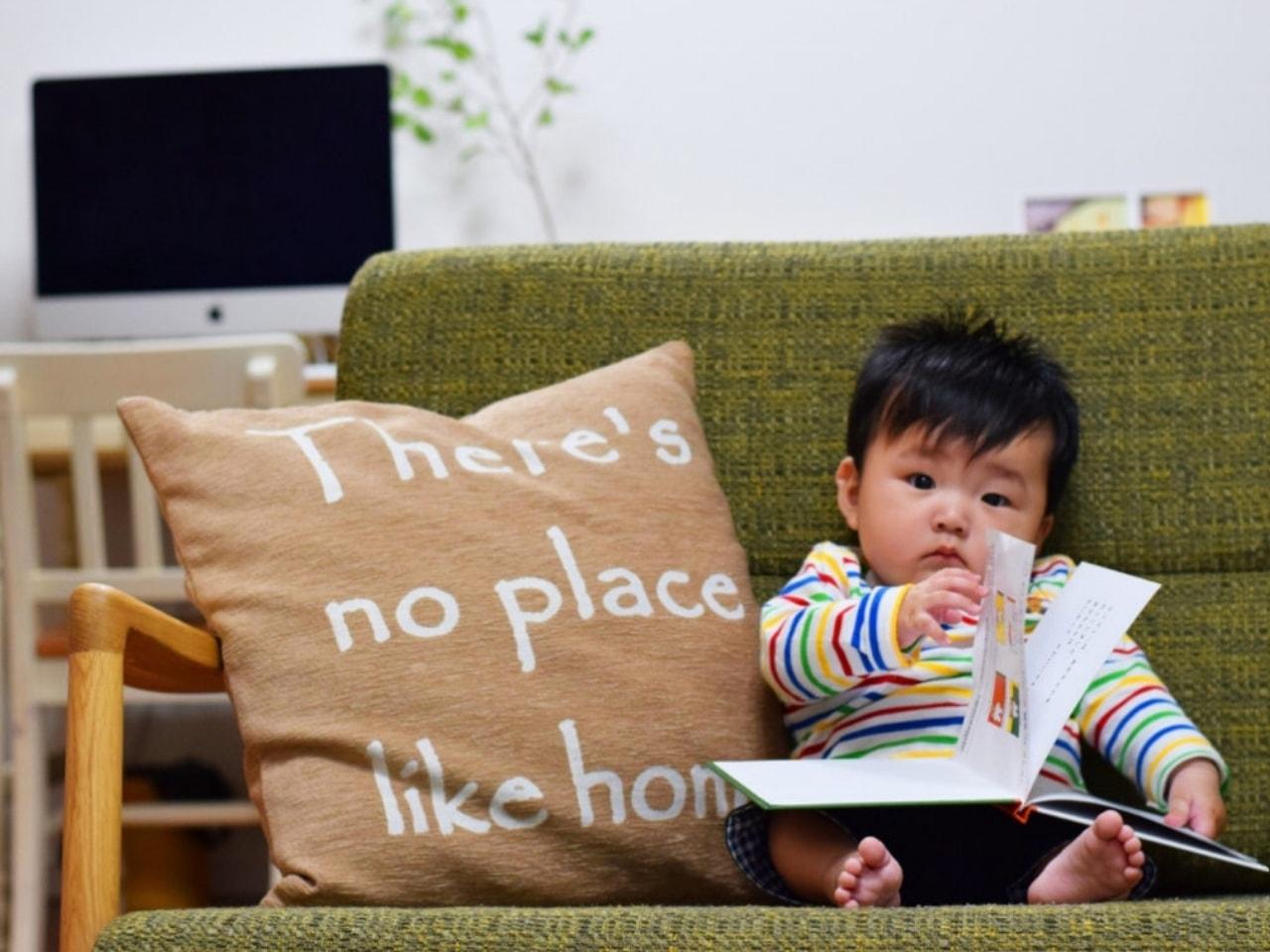 ソファーの上で絵本を読む赤ちゃん