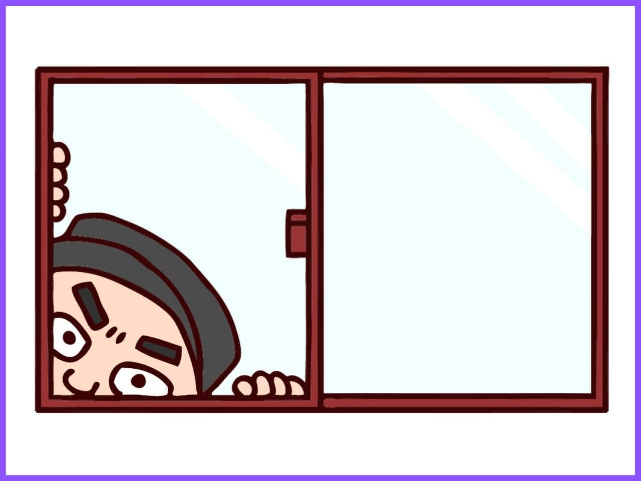 窓から家の中を見る泥棒