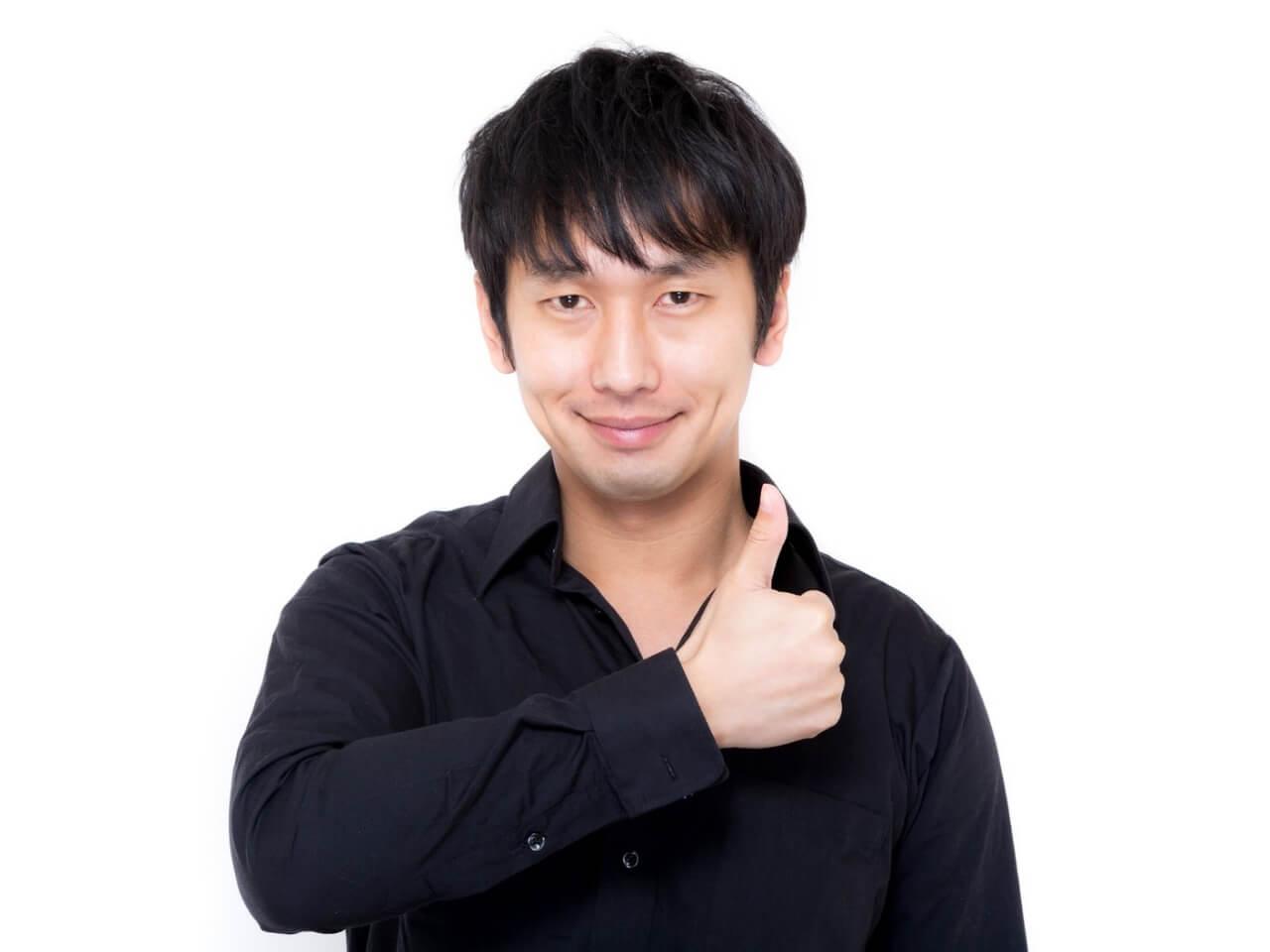 サムズアップする黒いシャツを着た男性