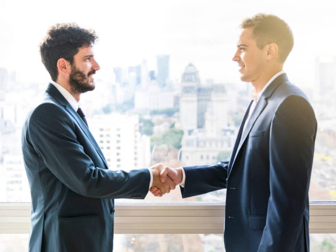 同じ目線で握手をする男性二人