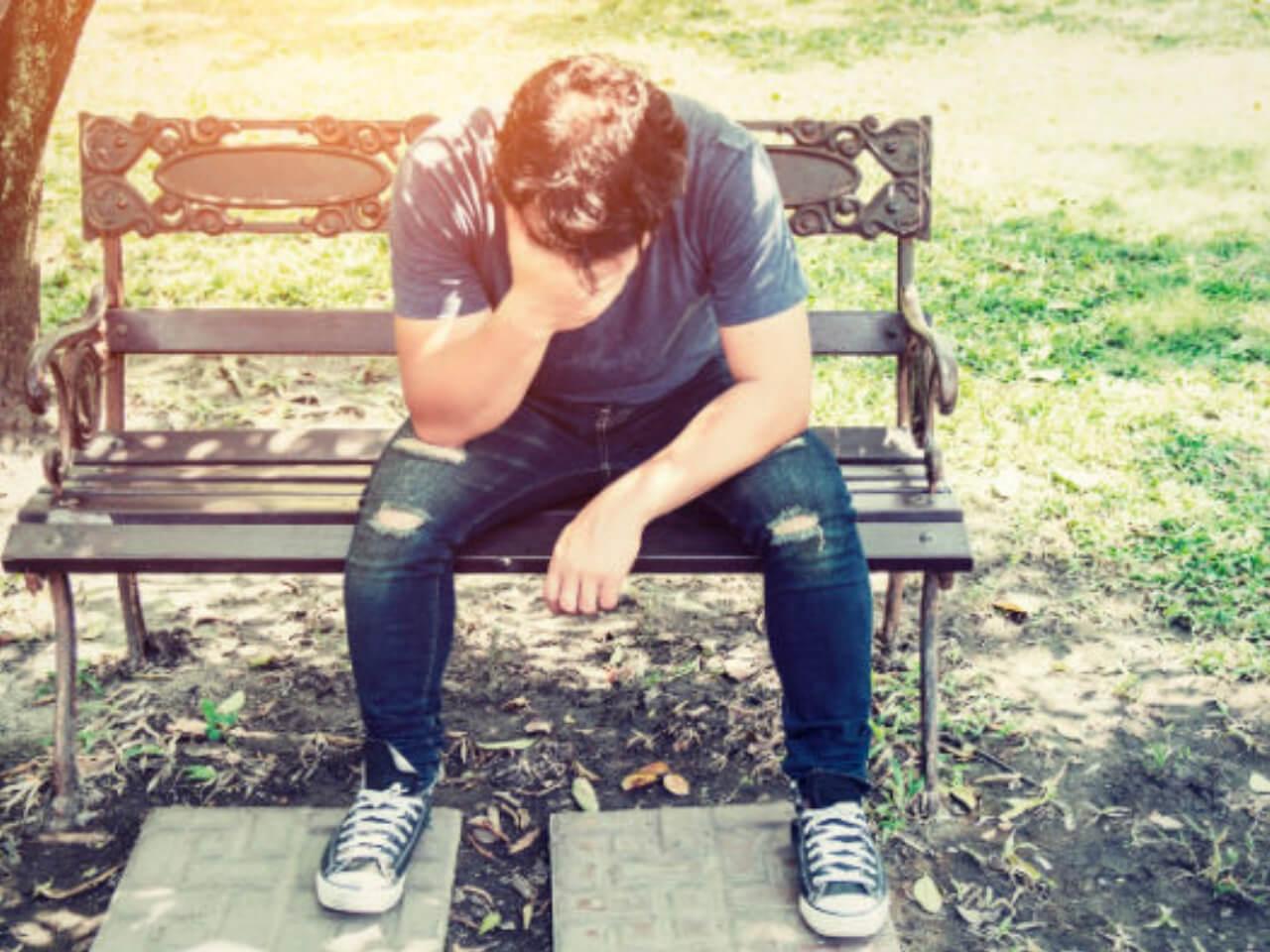 公園のベンチに座ってがっかりする男性