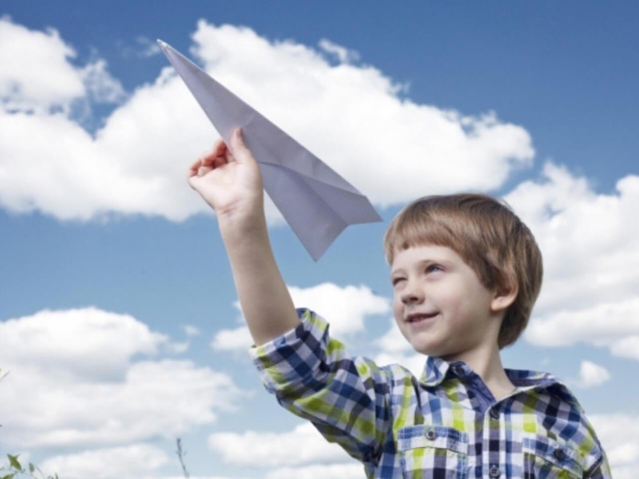 大きな紙飛行機を飛ばそうとする少年
