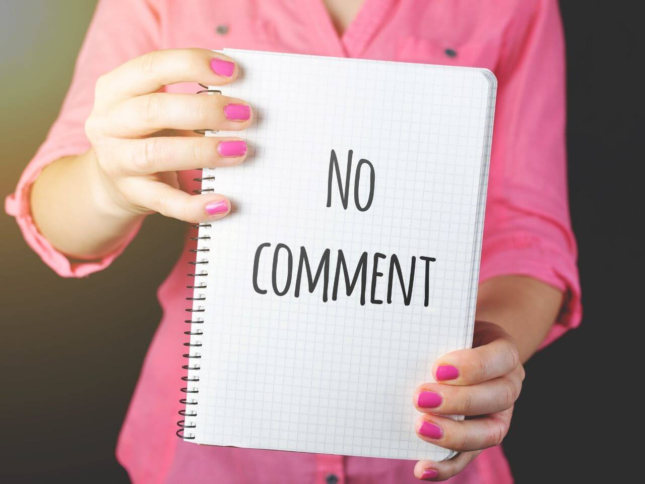 ノーコメントと書かれたノートを持つ人