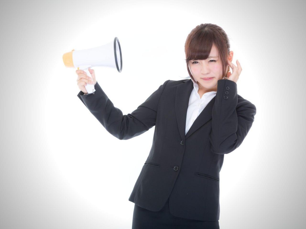 拡声器を持ってうるさそうにする女性
