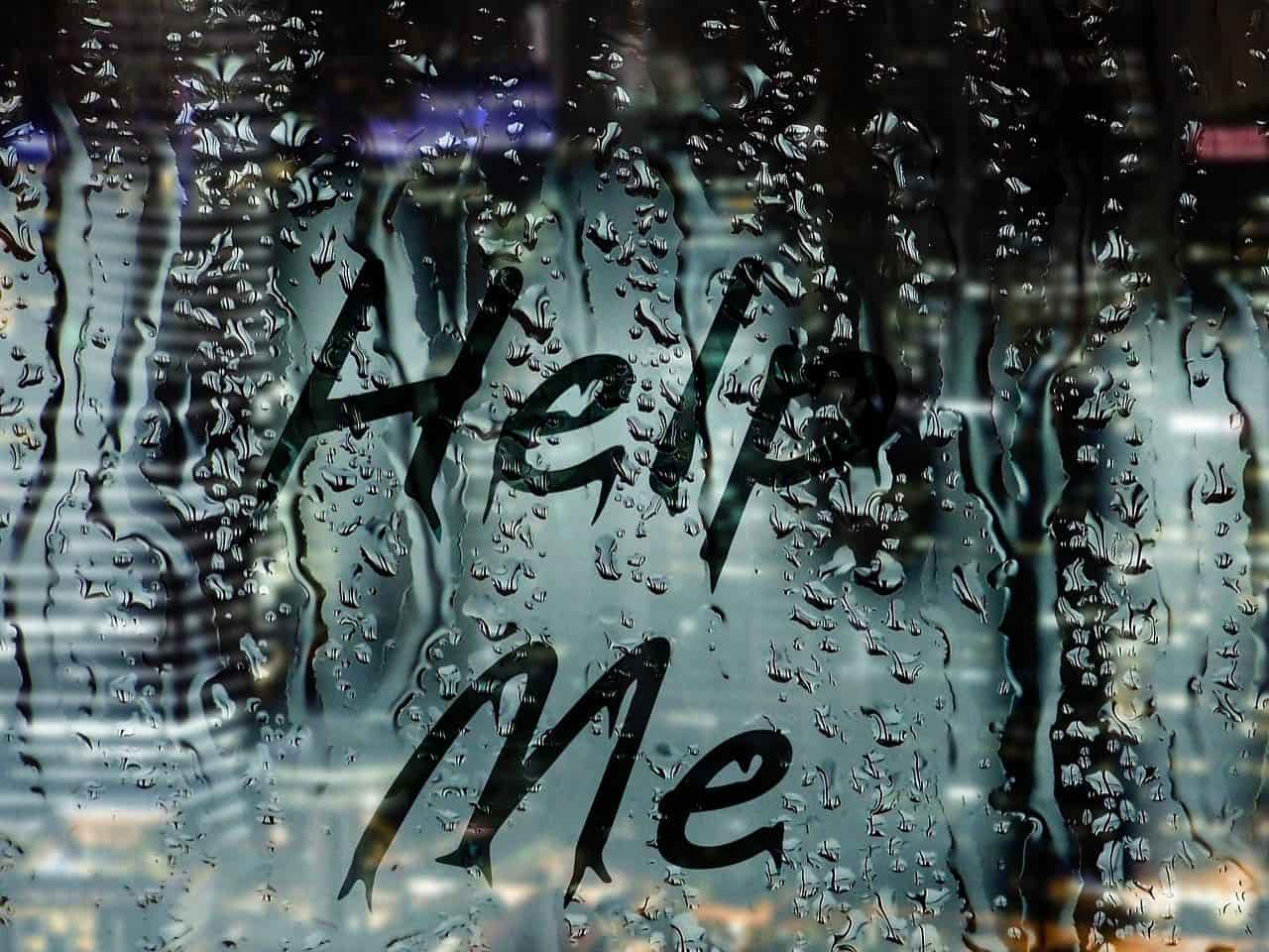 助けてと書かれた雨に濡れた窓