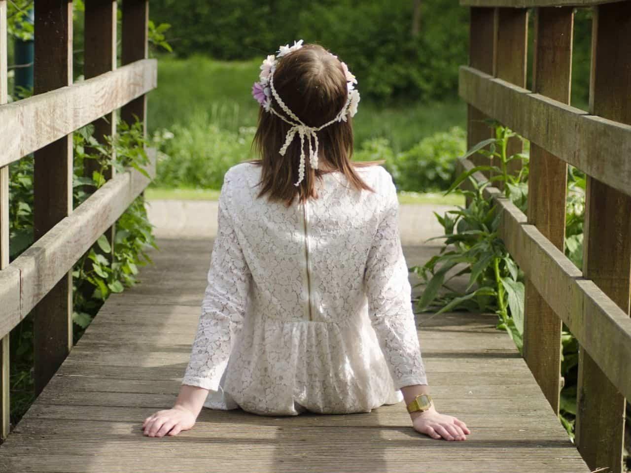 橋の上に座っている少女の後ろ姿