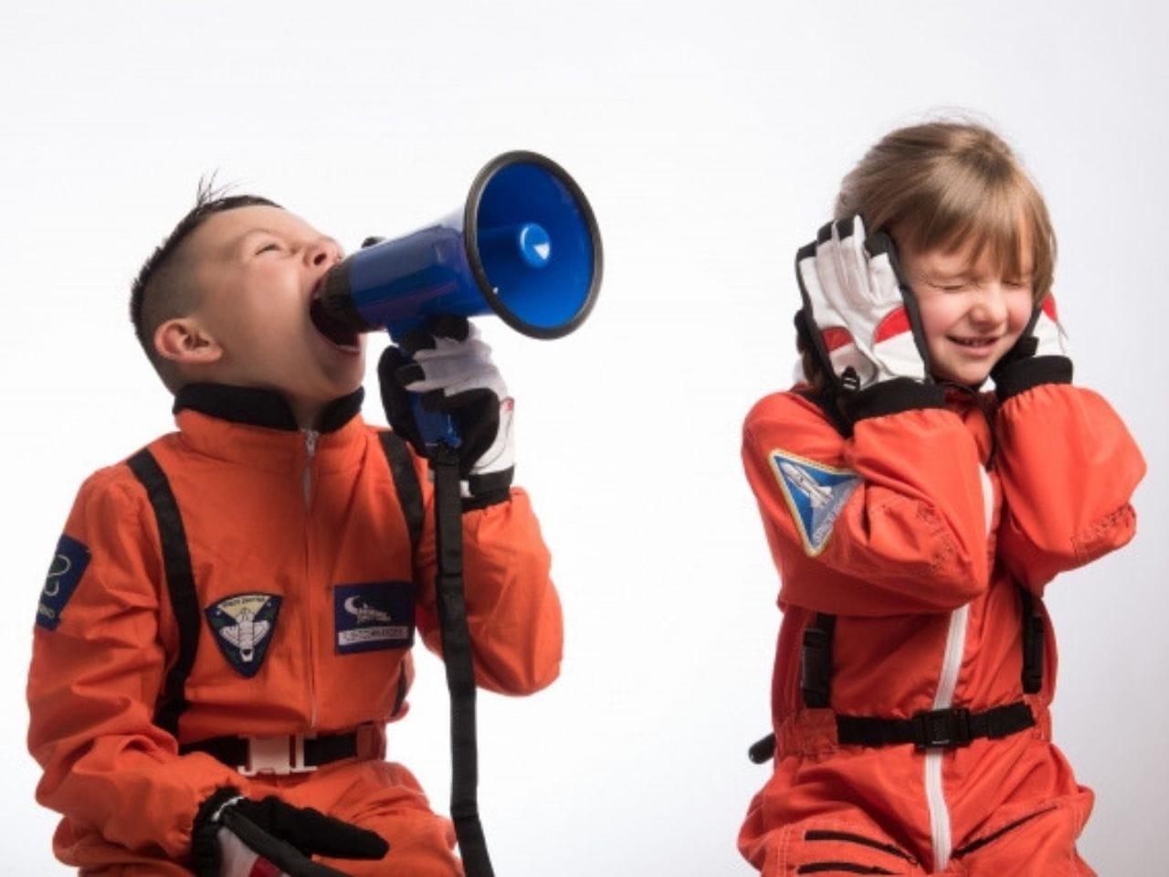 拡声器で騒音を出す少年と耳をふさぐ少女