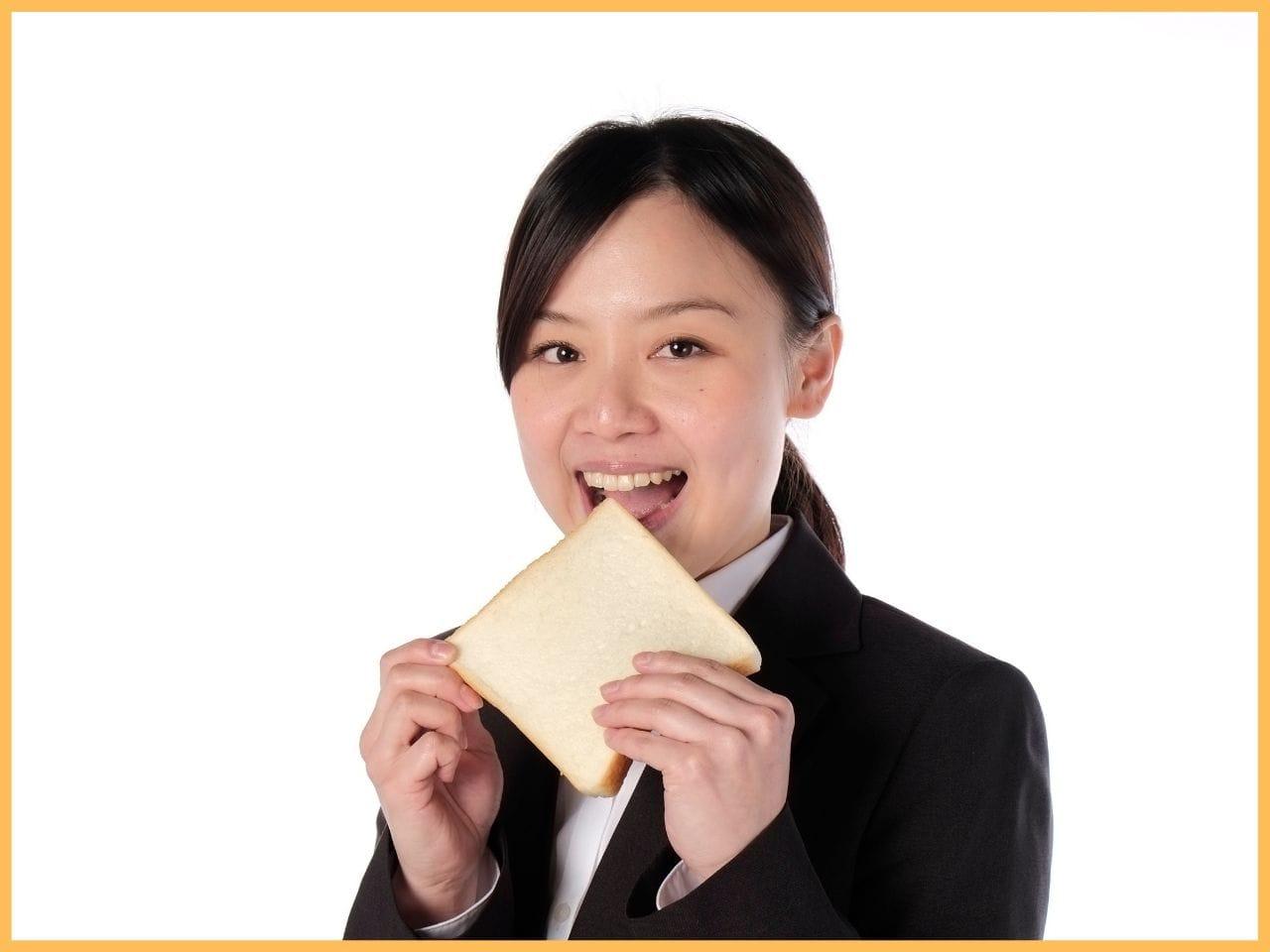 パンを食べるスーツ姿の女性