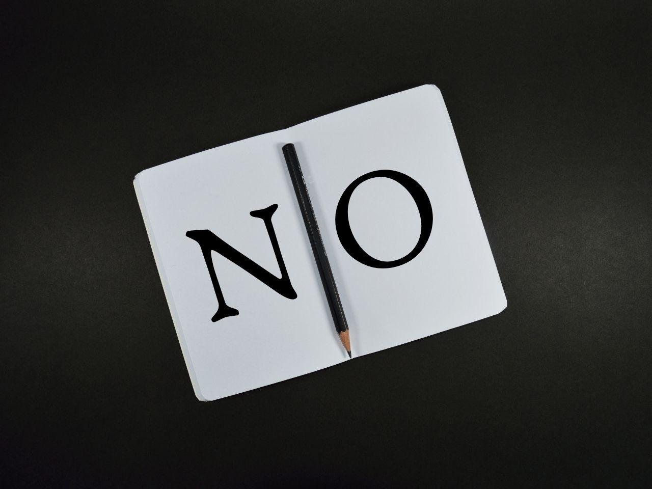 NOと書かれたカードと鉛筆