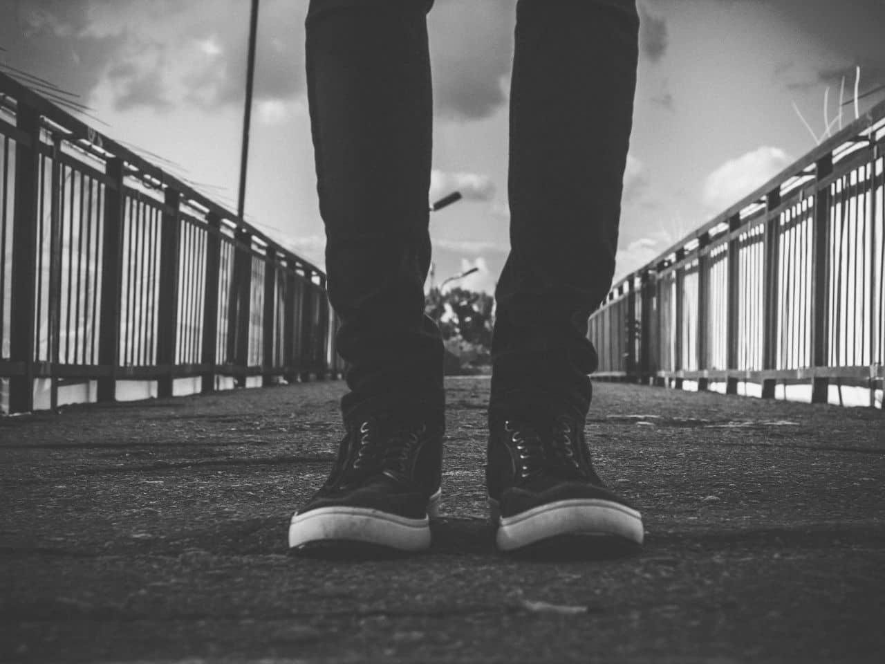 橋の上に立つ男性の両脚