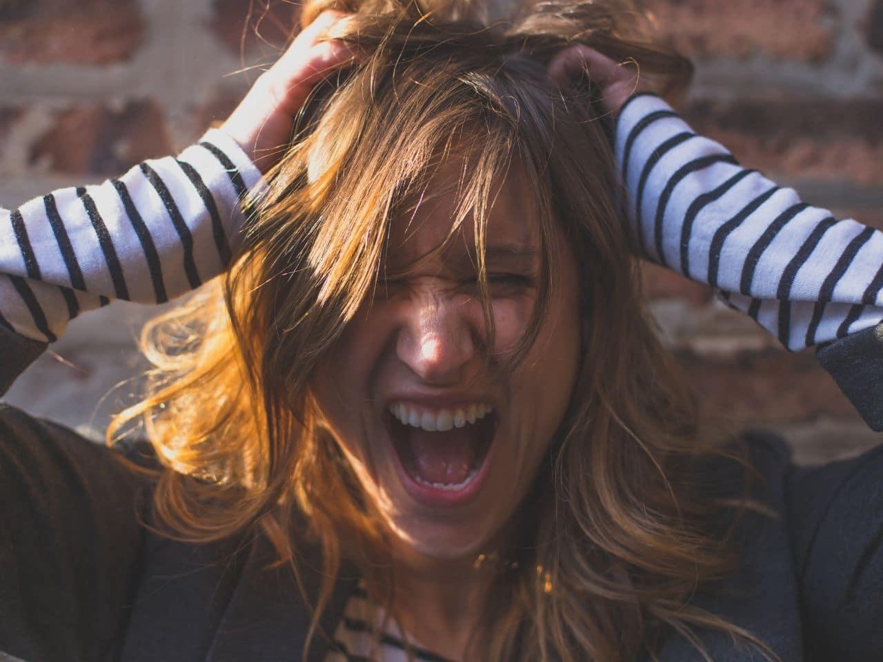 発狂して髪をかきむしる女性
