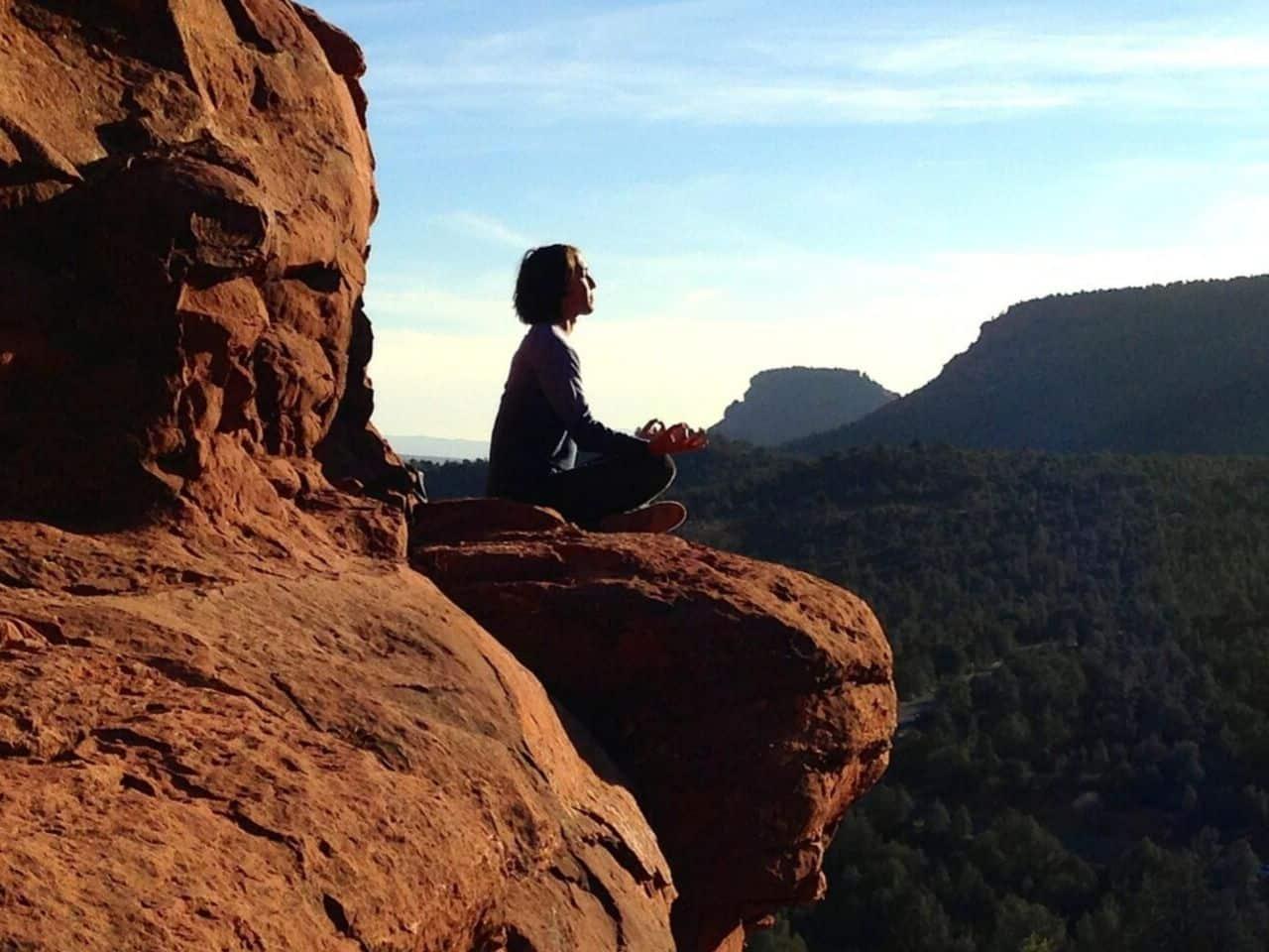 断崖絶壁で瞑想する女性