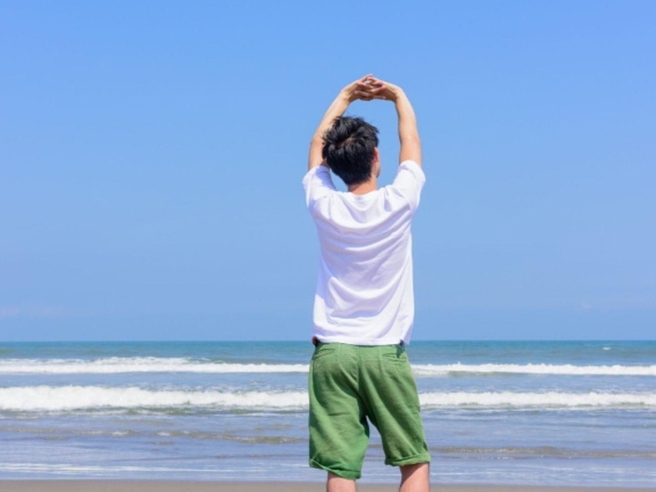快適そうに海で背伸びする男性