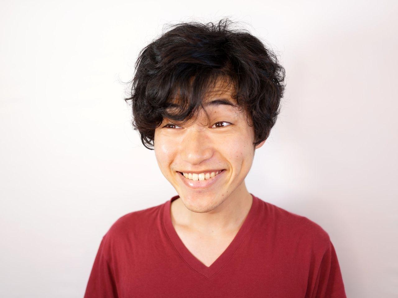 独特な表情で愛想笑いする男性