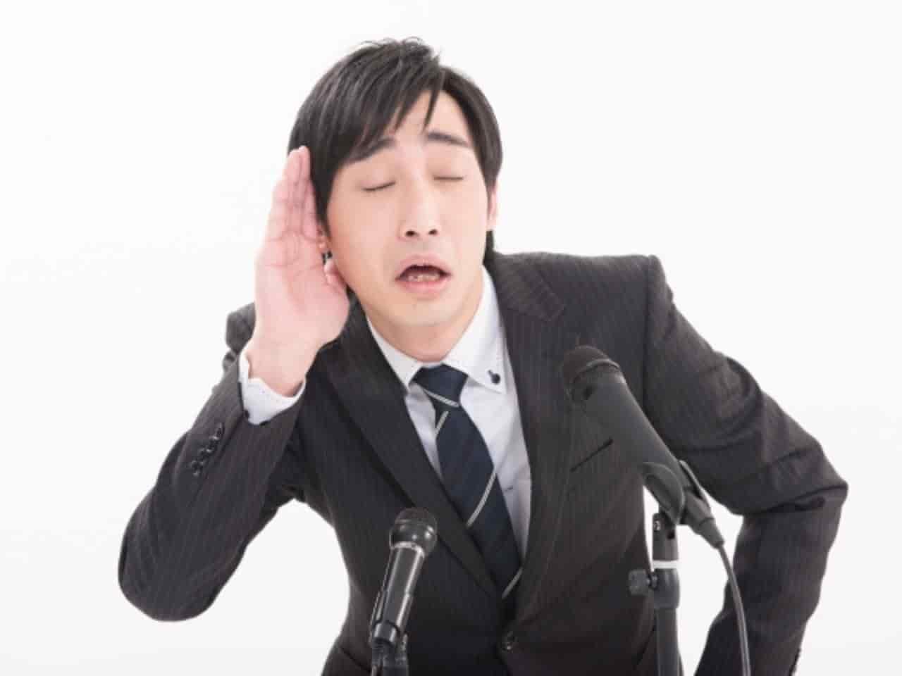 耳に手をあてて聞こえていないふりをする男性