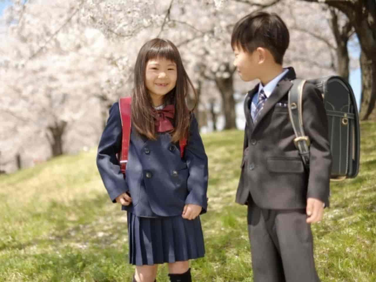 満開の桜の下で新入学を迎えるランドセルを背負った男の子と女の子