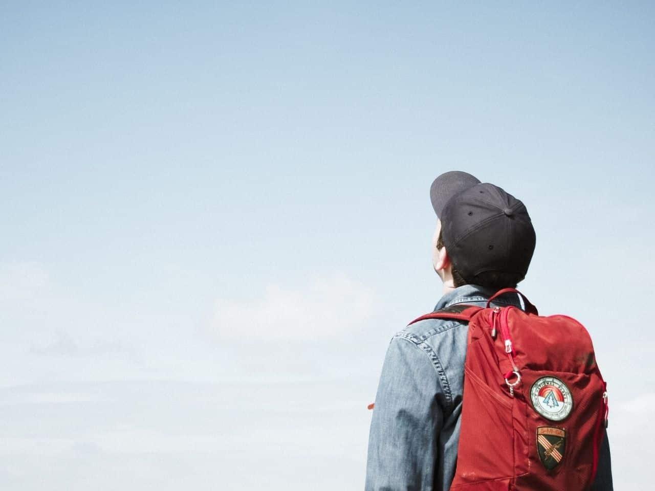 旅行に出かけて青い空を見上げる男性