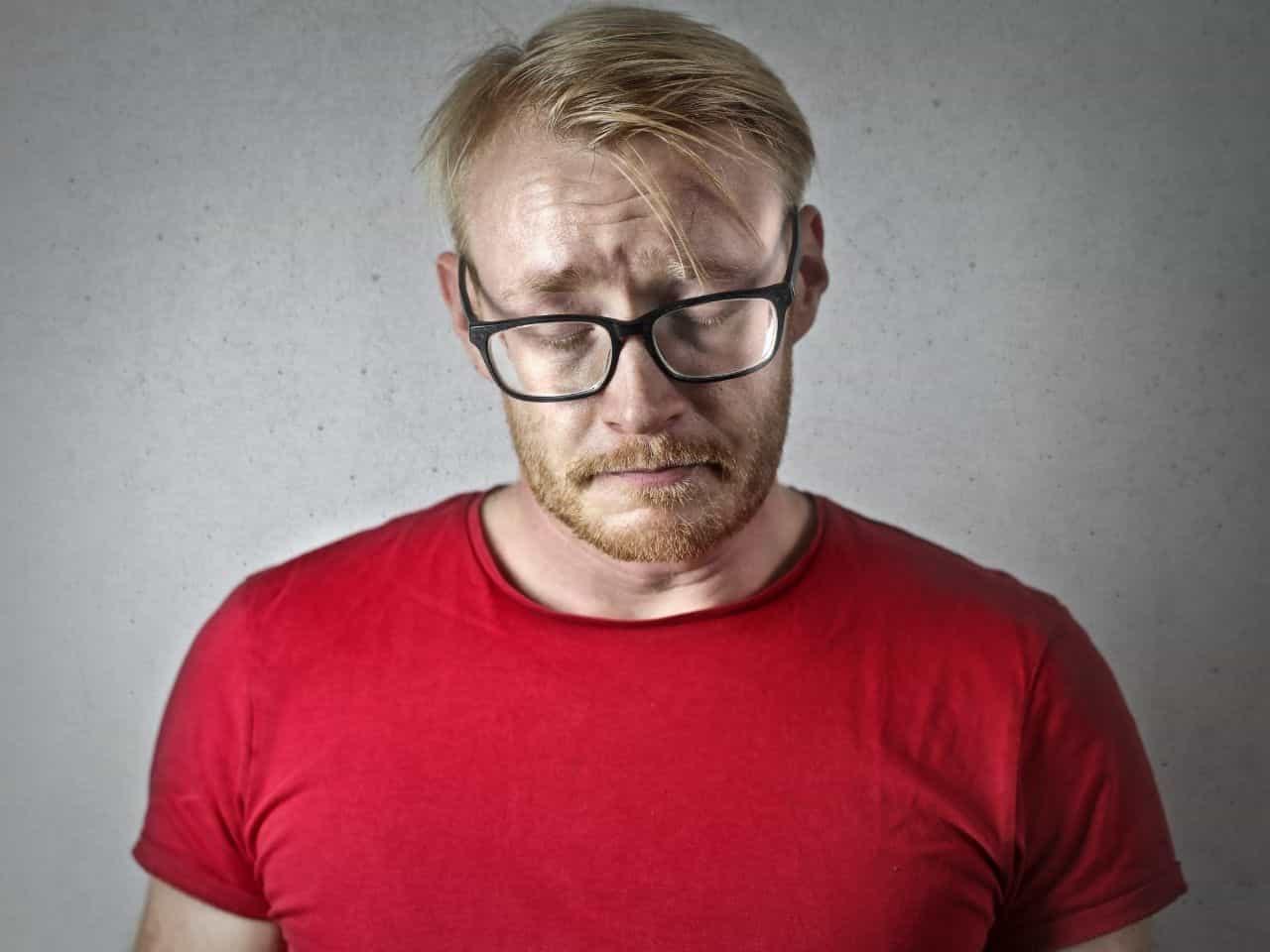 がっかりする赤いシャツを着た男性