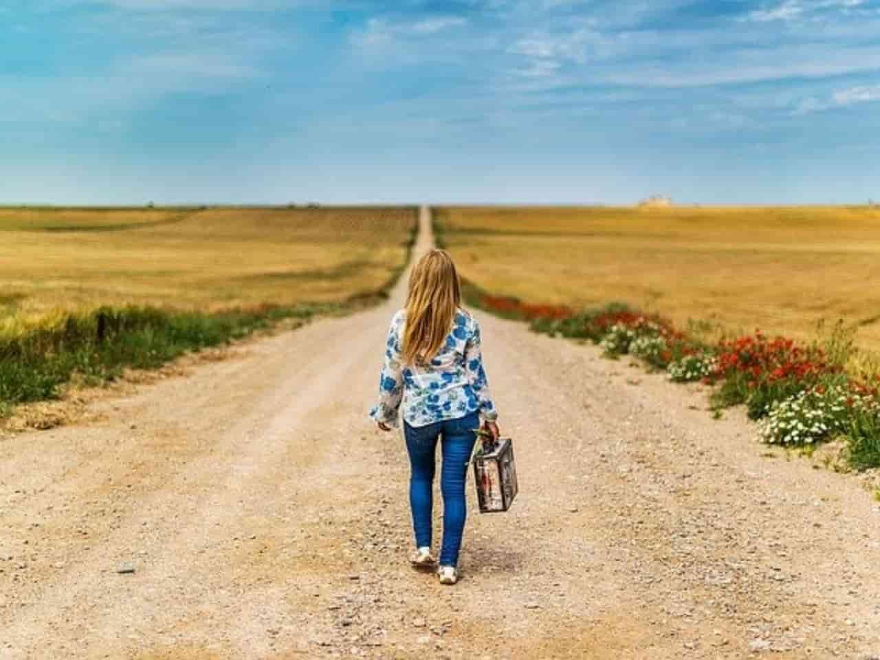 長い道を一人で歩く女性