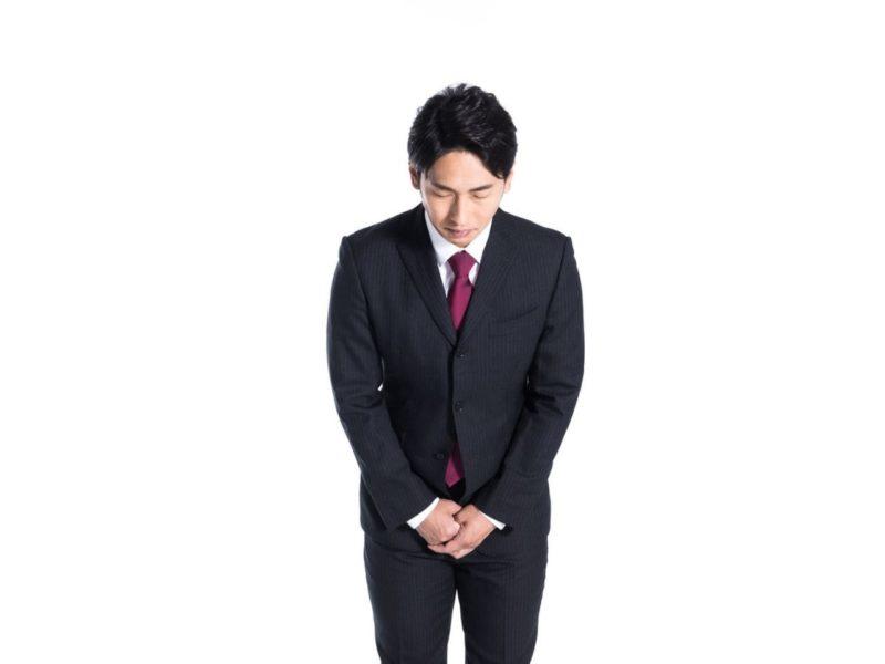 会釈して謝罪するスーツ姿の男性