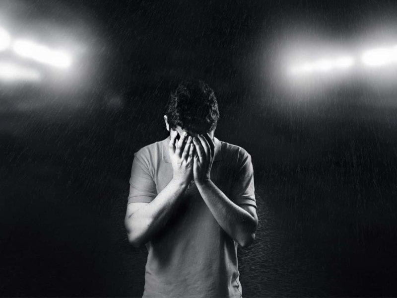 悲しく顔を覆う男性