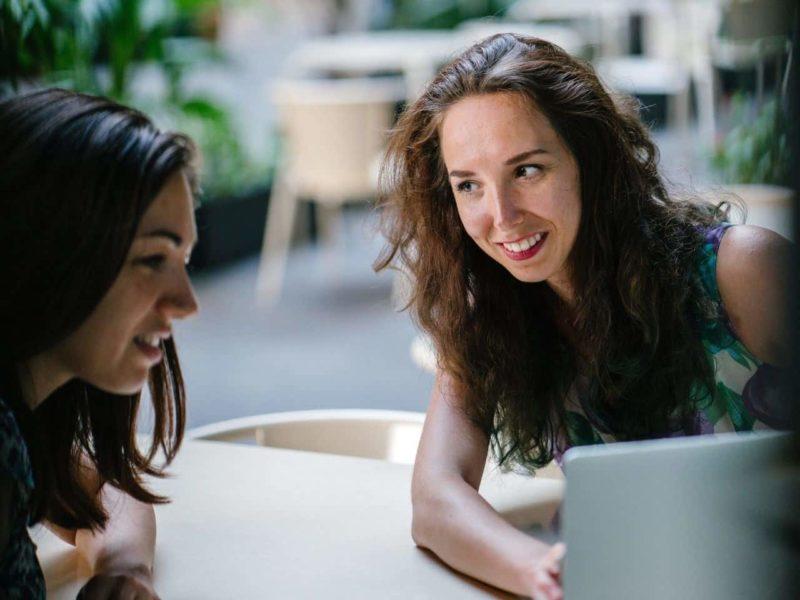 パソコンを見ながら話す二人の女性
