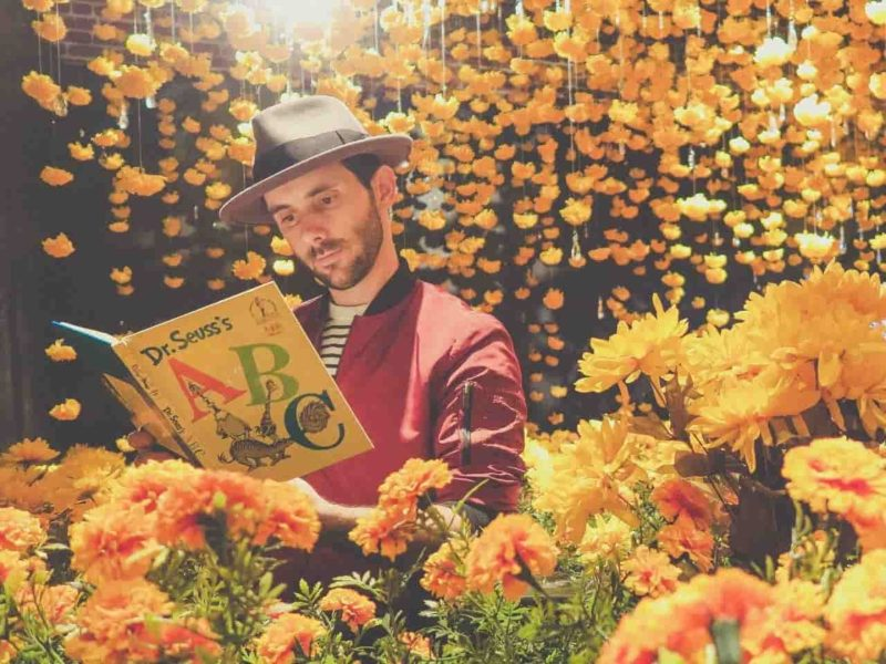 黄色の花の中で本を読む男性