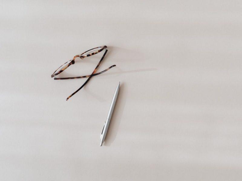 白いテーブルにあるメガネとペン