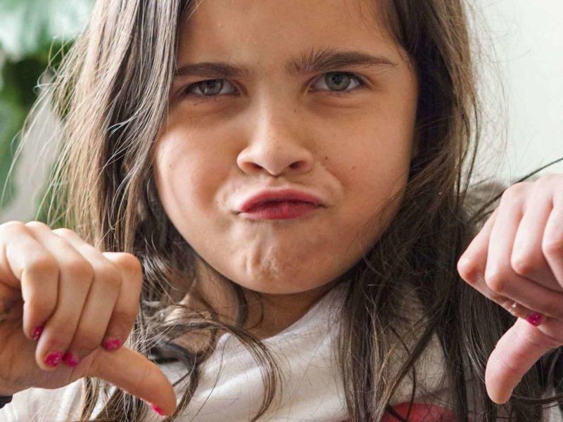 親指を下げて非難する少女