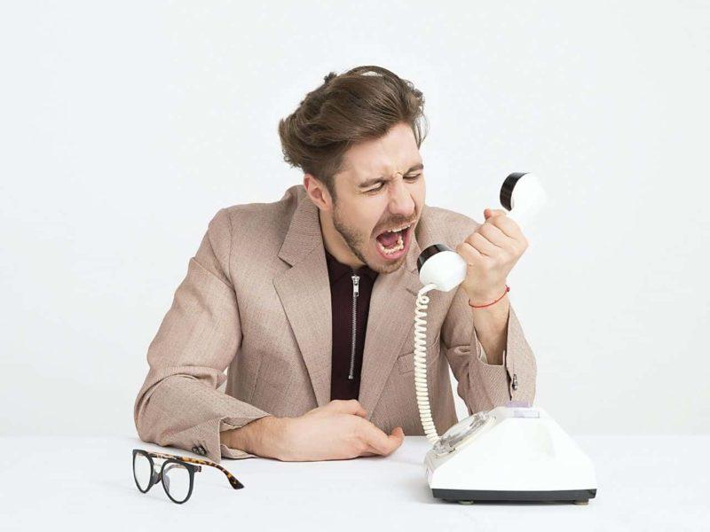 受話器に向かって怒鳴る男性