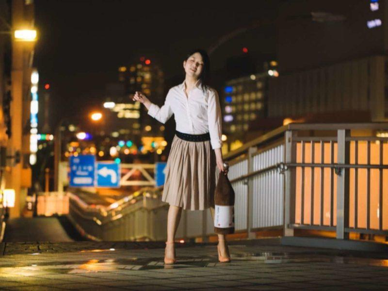 酔っ払って夜の街を歩く女性