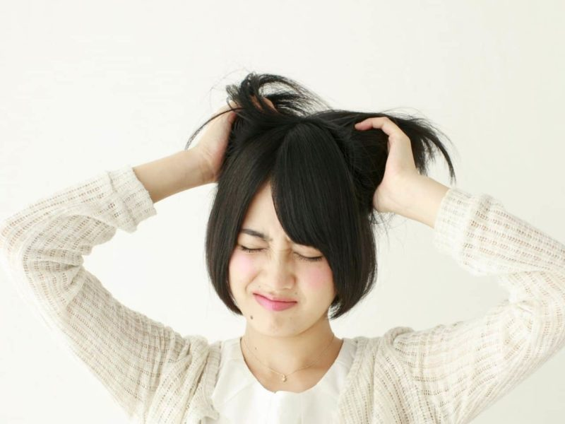 頭を掻きむしる女性