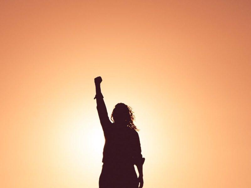腕を突き上げるアクティブな女性