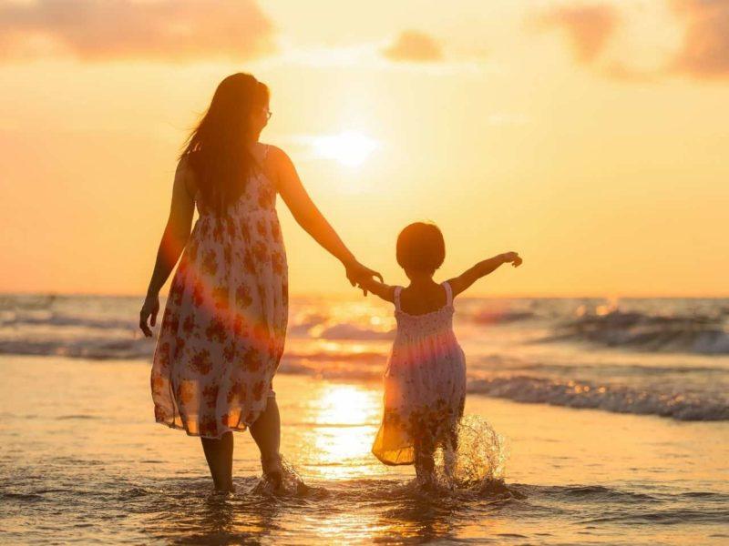 砂浜を歩く母親と女の子