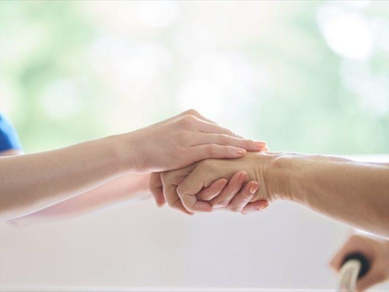 高齢者の手をつなぐ介護士